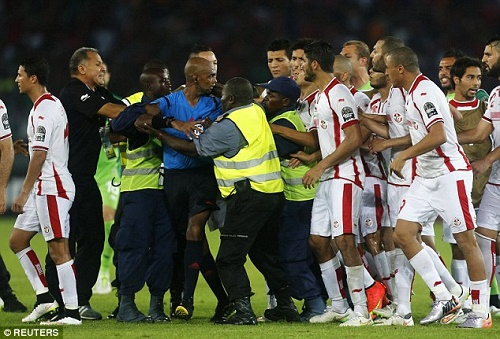 Tunisia players forward beat referee Rajindraparsad Seechurn after controversial penalty against Equatorial Guinea.